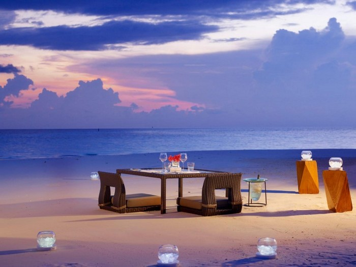 Outdoor-Dining-Table-On-Beach-With-Rattan-Chairs-And-Candle-Glass