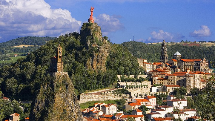 July 2007, Le Puy, France --- The church of St. Michel d'Aiquilhe atop the pinnacle of Rocher St. Michel, and a statue of the Virgin and Child atop the peak of Rocher Corneille overlook Le Puy, France. --- Image by © Jose Fuste Raga/Corbis